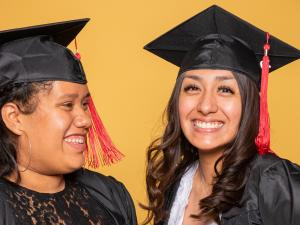 two female graduates smiling