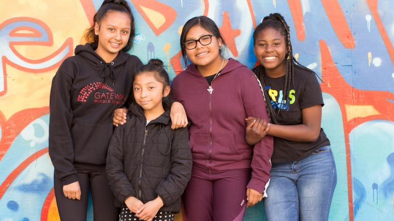 Middle school girls pose in front of a mural